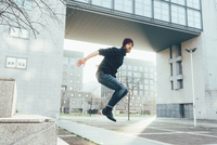 Young male hipster jumping mid air practicing parkour in city 11015327839| 写真素材・ストックフォト・画像・イラスト素材|アマナイメージズ
