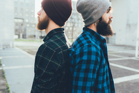 Portrait of two young male hipsters in knit hats back to back in city 11015327841| 写真素材・ストックフォト・画像・イラスト素材|アマナイメージズ