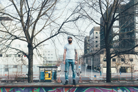 Portrait of cool young male hipster standing on wall 11015327843| 写真素材・ストックフォト・画像・イラスト素材|アマナイメージズ
