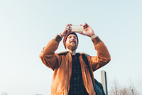 Happy young male hipster taking smartphone selfie against blue sky 11015327845| 写真素材・ストックフォト・画像・イラスト素材|アマナイメージズ