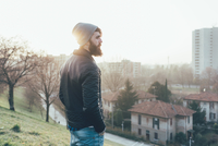 Young male hipster looking out over cityscape 11015327846| 写真素材・ストックフォト・画像・イラスト素材|アマナイメージズ