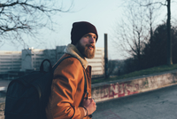 Young male hipster walking in park 11015327847| 写真素材・ストックフォト・画像・イラスト素材|アマナイメージズ