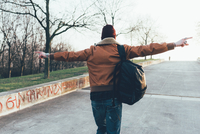 Rear view of young male hipster walking in park with arms out 11015327848| 写真素材・ストックフォト・画像・イラスト素材|アマナイメージズ