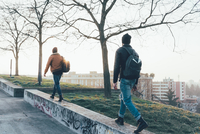 Rear view of two young male hipsters walking along park wall 11015327849| 写真素材・ストックフォト・画像・イラスト素材|アマナイメージズ