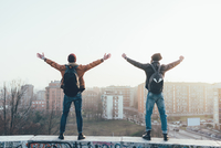 Rear view of two young male hipsters standing on city wall with arms out 11015327850| 写真素材・ストックフォト・画像・イラスト素材|アマナイメージズ