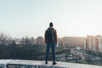 Rear view of young male hipster standing on city wall looking out 11015327852| 写真素材・ストックフォト・画像・イラスト素材|アマナイメージズ