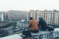 Rear view of two young male hipsters sitting on wall above cityscape 11015327855| 写真素材・ストックフォト・画像・イラスト素材|アマナイメージズ