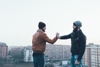 Two young male hipsters fist bumping above cityscape 11015327856| 写真素材・ストックフォト・画像・イラスト素材|アマナイメージズ
