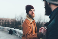 Two young male hipsters fist bumping in park 11015327857| 写真素材・ストックフォト・画像・イラスト素材|アマナイメージズ
