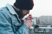 Young male hipster in knit hat igniting cigarette in city 11015327859| 写真素材・ストックフォト・画像・イラスト素材|アマナイメージズ