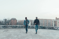 Two young male hipsters walk on city roof terrace 11015327860| 写真素材・ストックフォト・画像・イラスト素材|アマナイメージズ