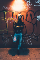 Portrait of cool young male hipster leaning against graffiti wall at night 11015327862  写真素材・ストックフォト・画像・イラスト素材 アマナイメージズ