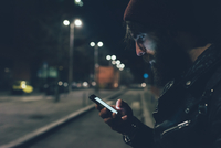 Young male hipster on city street looking at smartphone at night 11015327865  写真素材・ストックフォト・画像・イラスト素材 アマナイメージズ