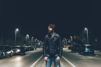 Young male hipster on city street looking away at night 11015327866  写真素材・ストックフォト・画像・イラスト素材 アマナイメージズ