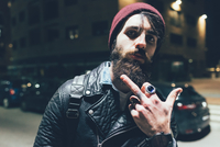 Portrait of young male hipster on city street at night giving obscene finger gesture 11015327867  写真素材・ストックフォト・画像・イラスト素材 アマナイメージズ