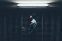 Young male hipster in dark city doorway at night 11015327869  写真素材・ストックフォト・画像・イラスト素材 アマナイメージズ