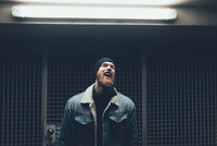 Young male hipster laughing in dark city doorway at night 11015327870  写真素材・ストックフォト・画像・イラスト素材 アマナイメージズ