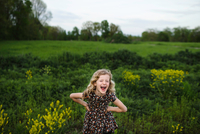 Portrait of girl with wavy blond hair laughing in field 11015327892| 写真素材・ストックフォト・画像・イラスト素材|アマナイメージズ