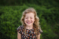 Portrait of girl with wavy blond hair and missing tooth in field 11015327894| 写真素材・ストックフォト・画像・イラスト素材|アマナイメージズ