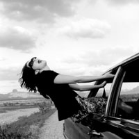 A woman hanging out a car window