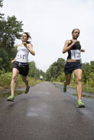 Two women running on road in sports race