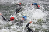 Group of triathletes swimming in lake