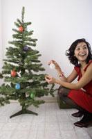 Woman crouching by Christmas tree