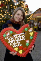 Woman holding up a heart shaped cookie 11016011887| 写真素材・ストックフォト・画像・イラスト素材|アマナイメージズ