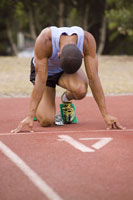 athlete in starting blocks on a track