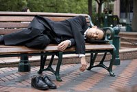 A businessman sleeping on a bench