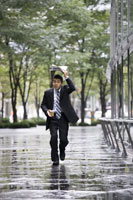 A businessman running in the rain