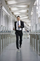 A businessman running along a corridor