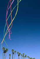 Colored streamers floating in the sky above palm trees