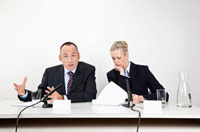 A man and a woman sitting at a desk with microphones and doc