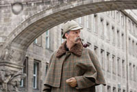 A man dressed up as Sherlock Holmes standing under a buildin