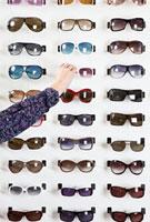 A human hand choosing a pair of sunglasses in an eyewear sto