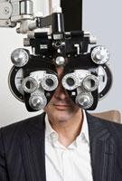 A man looking through a Phoropter during an eye exam