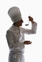 A chef holding a ladle up to his mouth,portrait