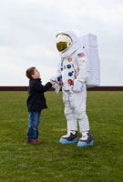 A boy shaking hands with an astronaut