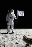 An astronaut standing next to a white flag 11016020156| 写真素材・ストックフォト・画像・イラスト素材|アマナイメージズ