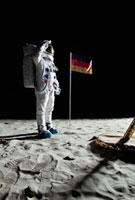 An astronaut standing near a lunar lander salutes an German