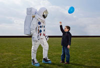 A boy holding out a balloon to an astronaut