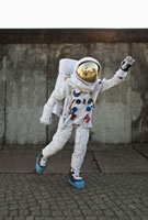 An astronaut on a city sidewalk pretending to take off in fl
