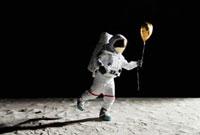 An astronaut on the moon holding a heart shaped helium ballo
