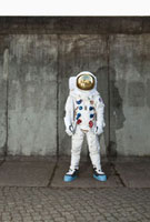 An astronaut standing on a sidewalk in a city