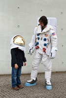 A boy in a space helmet looking up and standing next to an a
