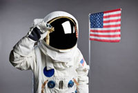 An astronaut saluting next to an American flag, studio shot