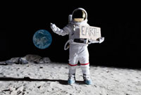 An astronaut on the moon with his thumb out, holding 'EART