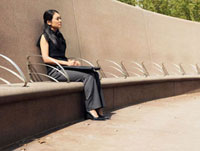 A businesswoman sitting on a cement bench