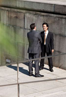Two businessmen talking, outdoors